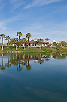 Large custom home is seen across golf course and adjascent lake