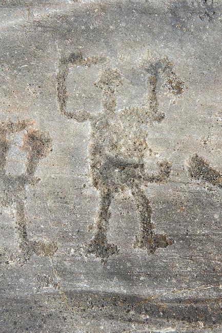 Petroglyph, rock carving, of a schematic human figure carved by the ancient Camuni people in the iron age between  900-1200 BC. Rock 26-27, Foppi di Nadro, Riserva Naturale Incisioni Rupestri di Ceto, Cimbergo e Paspardo, Capo di Ponti, Valcamonica (Val Camonica), Lombardy plain, Italy