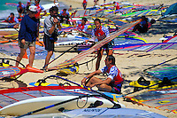 A cameraman films a windsurfer sitting at beach at the 1998 United States Windsurfing National Championships at Kanaha Beach Park on Maui's North Shore. This is a popular site even today for events including kiteboarding or kitesurfing.