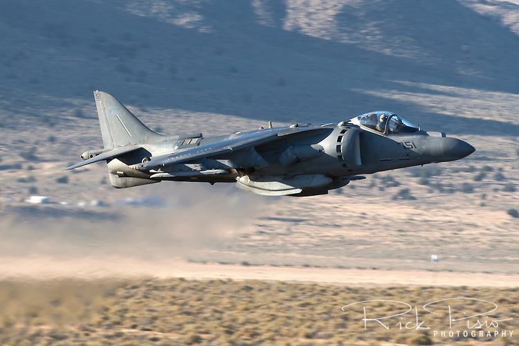 An AV-8B Harrier of the VX-9 Vampires in lowel level flight. Capable of vertical take off's and landings this subsonic fighter is utilized by the Marines as a light ground attack airplane. Powered by a Rolls Royce F402-RR-408 Pegasus vectored thrust turbofan the aircraft has a maximum speed of 629 mph with a range of 685 miles,  Based in China Lake, California, The VX-9 Vampires mission includes operational evaluation of attack, fighter, and electronic warfare aircraft, weapons systems and equipment, and to develop tactical procedures for their employment.