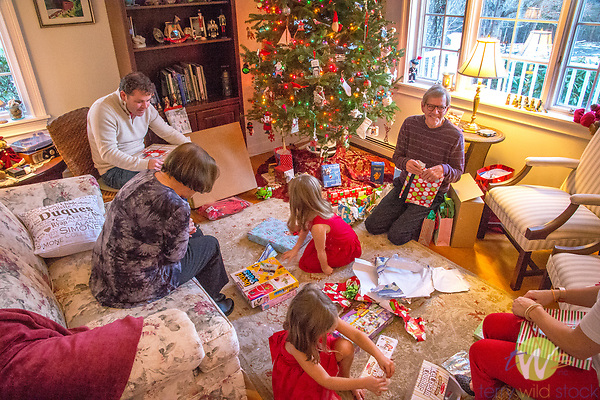 Family in living room on Christmas morning opening gifts.