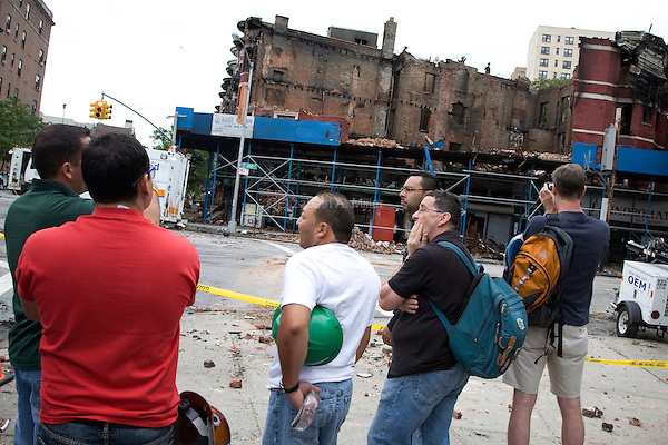 People observe the aftermath of a four-alarm fire on Saturday, 04 June 2011 that broke out on the corner of St. Johns Place and Washington Avenue in Prospect Heights, Brooklyn, New York around 4:30am Saturday morning.