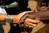 Banjul, The Gambia. White woman's hand with silver bracelet shaking a weathered black hand.