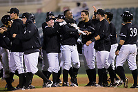 Micker Adolfo (center) is congratulated by his teammates after his walkoff single in the bottom of the ninth inning against the Asheville Tourists at Kannapolis Intimidators Stadium on May 6, 2017 in Kannapolis, North Carolina.  The Intimidators walked-off the Tourists 7-6.  (Brian Westerholt/Four Seam Images)