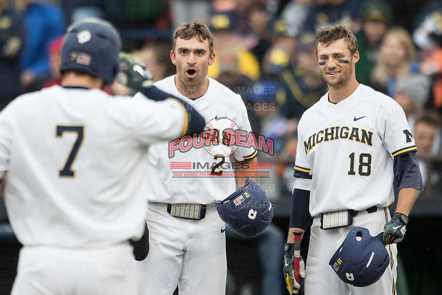 Michigan Wolverines outfielder Jonathan Engelmann (2) waits at the plate with teammate Jake Bivens (18) as Harrison Wenson (7) heads home after blasting a home run against the Michigan State Spartans on May 19, 2017 at Ray Fisher Stadium in Ann Arbor, Michigan. Michigan defeated Michigan State 11-6. (Andrew Woolley/Four Seam Images)