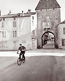 FRANCE, Burgundy, man riding bicycle carrying bread in old town, Noyers (B&W)