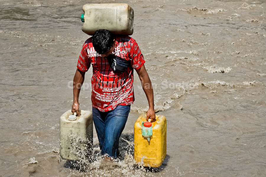 A contraband smuggler carries three barrels of gasoline (90 kg) across the river Tachira on the Colombia-Venezuela border, 2 May 2006. Venezuelan gasoline, being 20 times cheaper than in Colombia, is the most wanted smuggling item, followed by food and car parts, while reputable Colombian clothing flow to Venezuela. There are about 25,000 barrels of gasoline crossing illegally the Venezuelan border every day. The risky contraband smuggling, especially during the rainy season when the river rises, makes a living to hundreds of poor families in communities on both sides of the frontier.