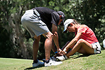 HOUSTON, TX - MAY 12: Rhodes College on course coach, Sam Kern helps put a band aid on player Sarahanne Vaughan during the Division III Women's Golf Championship held at Bay Oaks Country Club on May 12, 2017 in Houston, Texas. (Photo by Rudy Gonzalez/NCAA Photos/NCAA Photos via Getty Images)