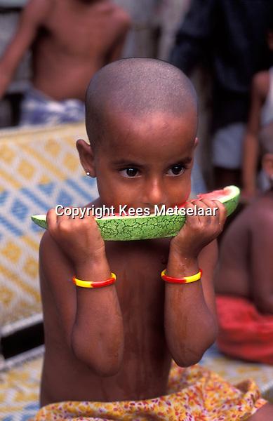Bangladesh, Dhaka, 1991..Child eating watermellon...Kind eet watermeloen...Photo Kees Metselaar