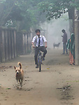 A boy rides his bicycle to school in the village of Suihari in northern Bangladesh.