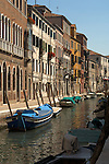 Colourful terraced houses on canal with boats tied to moorings. Venice Italy.