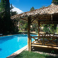 An eastern style bamboo bed with a thatched roof provides shaded seating beside an outdoor swimming pool.