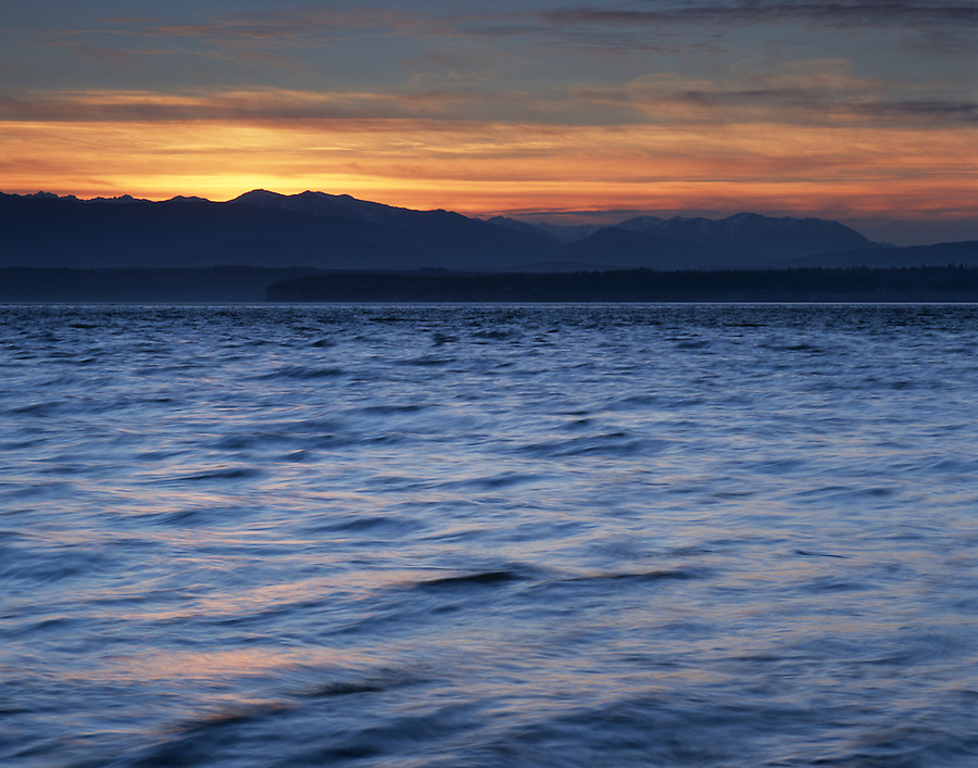 The waves along the shore of Bush Point in Whidbey Island, Washington provide a serene view of the sun setting behind the Olympic mountain range.