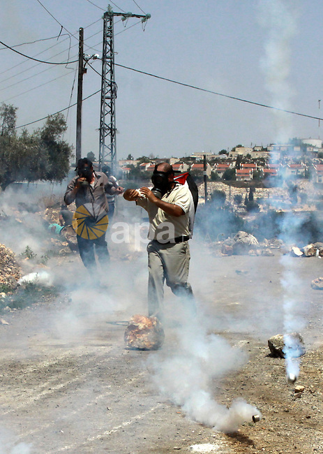 Palestinian protesters seek for cover from tear gas fired by Israeli security forces during clashes following a weekly protest against the expropriation of Palestinian land by Israel in the West Bank village of Kfar Qaddum, near Nablus on June 20, 2014. Photo by Nedal Eshtayah
