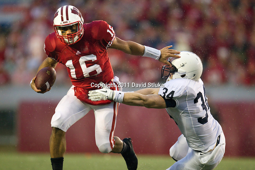 Wisconsin Badgers quarterback Russell Wilson (16) stiff arms Penn State Nittany Lions linebacker Nathan Stupar (34) during an NCAA Big Ten Conference college football game on November 26, 2011 in Madison, Wisconsin. The Badgers won 45-7. (Photo by David Stluka)