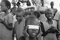 Sudan. Southern part. Bahr El Ghazal. Marial Lou. Dinka tribe area. Catholics celebrate mass and pray on sunday morning. A small boy plays with a piece of white paper and covers his eyes.  © 1998 Didier Ruef