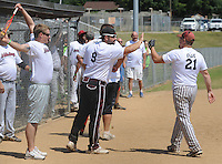NWA Democrat-Gazette/ANDY SHUPE<br /> Dennis Donahue Jr. (9), a maintenance worker for Tyson Foods, gives a high five to teammates Saturday, Aug. 15, 2015, as his team scores at the end of the game during the 33rd annual Tyson Foods Corporate Softball Tournament at the Randal Tyson Sports Complex in Springdale.