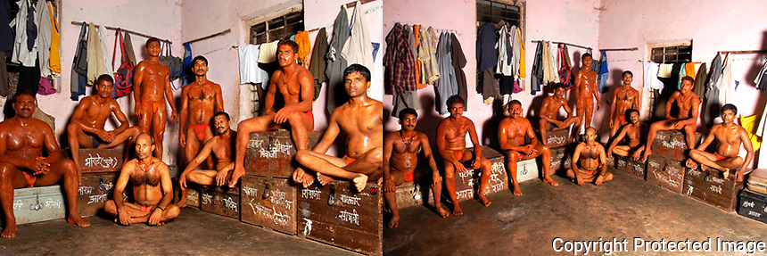 """Each wooden or aluminium trunk on which the wrestler is sitting is their temporary """"HOME"""", so to speak. The trunk prominently displays the name of the owner of the trunk and it contains all the belongings of that particular wrestler. Most of the wrestlers come from poor  rural backgrounds and find it hard to afford a house in the cities. They have temporary jobs like daily wage laborers in the wholesale food grain and vegetable markets. They work by day and practice wrestling in the evenings. The Akhara Kusti center doubles up as their staying place Mumbai."""