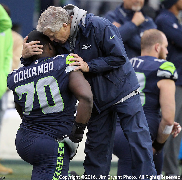 Seattle Seahawks head coach Pete Carroll whispers encouragement to offensive guard Rees Odhiambo (70)  before their game against thet Philadelphia Eagles<br /> at CenturyLink Field in Seattle, Washington on November 20, 2016.  Seahawks beat the Eagles 26-15.  &copy;2016. Jim Bryant Photo. All Rights Reserved.