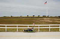 Morehead City, NC -- Quadriplegic hand cyclist Paul Kelly, 62, passes Ft. Macon as he trains for the Boston Marathon Tuesday, March 27, 2018. (Justin Cook for The Wall Street Journal)<br /> <br /> SUMMARY:<br /> <br /> Paul Kelly, hand cyclist, Beaufort, NC Training for the Boston Marathon so we would want to shoot in March to run the week before the marathon or marathon Monday, Apriln16. Life as a quadriplegic doesn&rsquo;t keep 62-year-old Paul Kelly on the sidelines. After breaking his neck in a swimming accident in 1978, Kelly was determined to find fitness activities to maintain an active lifestyle. He discovered handcycles while watching his niece compete in the 2006 Marine Corps Marathon and was inspired to start his own marathon career to stay fit. Paul has competed in over 100 half and full marathons. On April 16, he will celebrate his 40th year of living as a quadriplegic by taking on one of the most coveted races for a marathoner -- the Boston Marathon. Kelly is among the 60 handcyclists competing in the 2018 Boston Marathon with a qualifying time of 1:26:37. Most of Paul&rsquo;s distance training takes place at Bogue Banks, which includes Atlantic Beach, Salter Path, and Emerald Isle, N.C. It&rsquo;s Nicholas Sparks worthy scenery with its marshes, waterways, inlets and small islands. Paul is particularly fond of the approach from Atlantic Beach to Bogue Banks -- it&rsquo;s via the high-rise bridge. In cold weather, Paul has to be mindful of the environment and dress in a manner that insulates his legs while also allowing his upper body to ventilate. Paul chooses to train at times of day when the temperatures are more reasonable. He uses hand warmers in his gloves, on the inside the grips on his handcycle and in the legs of his trousers.