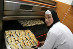 A Palestinian women prepare sweets for kindergartens at a bakery under the project of making work opportunities in the Gaza Strip town of Deir al-Balah on Feb 11,2010.this project has been executed by Mercy Corps Association. Photo by Ashraf Amra