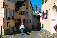 Man walking his Bernese Mountain dog in the Engadine Valley in the village of Guarda in Switzerland