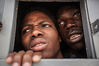 Sub-Saharan illegal migrants peer through the window of a cell as they wait for the guards to distribute food to the inmates in the Surman detention centre, northwest Libya.