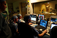 San Francisco, California, January 6, 2011 - From left, Dr. Alexander Papanastassiou (standing), a visiting doctor from the University Texas Health Science Center San Antonio, chief resident Mark Richardson, Alastair Martin PhD in the Department of Radiology and neurologist Paul Larson MD monitor the iMRI procedure of patient Linda Sharpe during an iMRI surgery at University of California San Francisco Medical Center. The MRI machine photographs the patient during the surgery allowing the doctors operating to view the procedure as well as support doctors and technicians to monitor from an outside room.  The iMRI procedure uses Deep brain stimulation (DBS), which has been used for over a decade to treat movement disorders such as Parkinson's disease, essential tremor, and dystonia. DBS uses a pulse generator implanted in the chest, similar to a pacemaker, to deliver pulses to specific regions of the brain via a permanently implanted electrode. In the U.S., DBS is normally done while the patient is awake, because the surgeon needs to induce the symptoms (like the involuntary movements of Parkinson's) to know if he's in the right place, and if the patient is unconscious, the symptoms can't be induced. Many patients find it hard to tolerate. Their head is clamped in a frame, they're aware of their surroundings, and the surgeon is deliberately producing tremors and twitches while they lie there...Interventional MRI (or iMRI) allows surgeons to implant these electrodes while the patient is unconscious taking advantage of MR imaging in real time by performing procedures inside the scanner itself. Doctors Paul Larson MD, and Philip Starr MD, PhD were both involved with this technology during its development in the 1990s. In 2002 they began to think about how to perform DBS using this technique at UCSF. Working with Alastair Martin PhD in the Department of Radiology, Jill Ostrem MD in the Department of Neurology, and others, they developed a technique of implantation using a