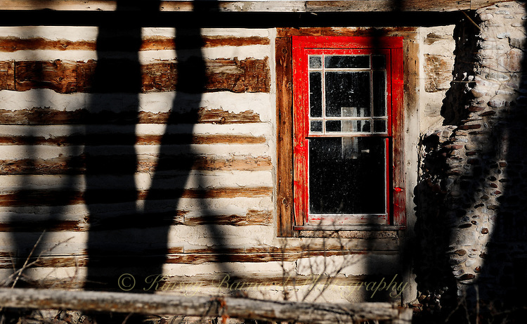 Chinking, shadows, and a red window frame showcase this photo taken at Bannack Ghost Town and Montana State Park