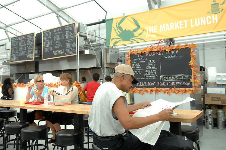 Allen Coaxum reads a newspaper during lunch at Market Lunch in Eastern Market's temporary location.