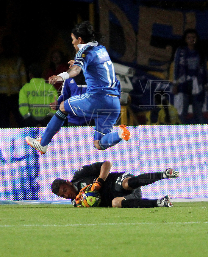 BOGOTA- COLOMBIA -05 -04-2014: Dayro Moreno (Izq.) jugador de Millonarios disputa el balón con Luis Hurtado (Der.) jugador de Deportivo Cali durante partido entre Millonarios y Deportivo Cali por la fecha 15 entre de la Liga Postobon I 2014, jugado en el estadio Nemesio Camacho El Campin de la ciudad de Bogota. / Dayro Moreno (L) player of Millonarios Fe vies for the ball with Luis Hurtado (R) player of Deportivo Cali during a match between Millonarios and Deportivo Cali for the date 15th of the Liga Postobon I 2014 at the Nemesio Camacho El Campin Stadium in Bogota city. Photo: VizzorImage  / Nestor Silva / Cont.