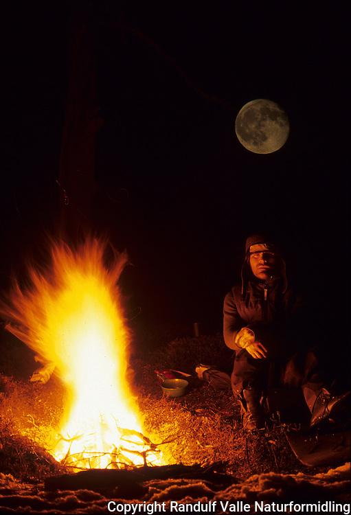 Mann hviler foran stort furubål en vårkveld ---- Man resting in front of large camp fire