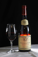 A bottle of Maison Louis Jadot Bourgogne Pinot Noir 2004 red burgundy wine and a glass of red wine standing on a table top with a white cloth. Backlit backlight back light lit Black background, Maison Louis Jadot, Beaune Côte Cote d Or Bourgogne Burgundy Burgundian France French Europe European