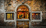 The windows of a boutique hotel overlook a canal in the sestiere of San Marco in Venice, Italy.