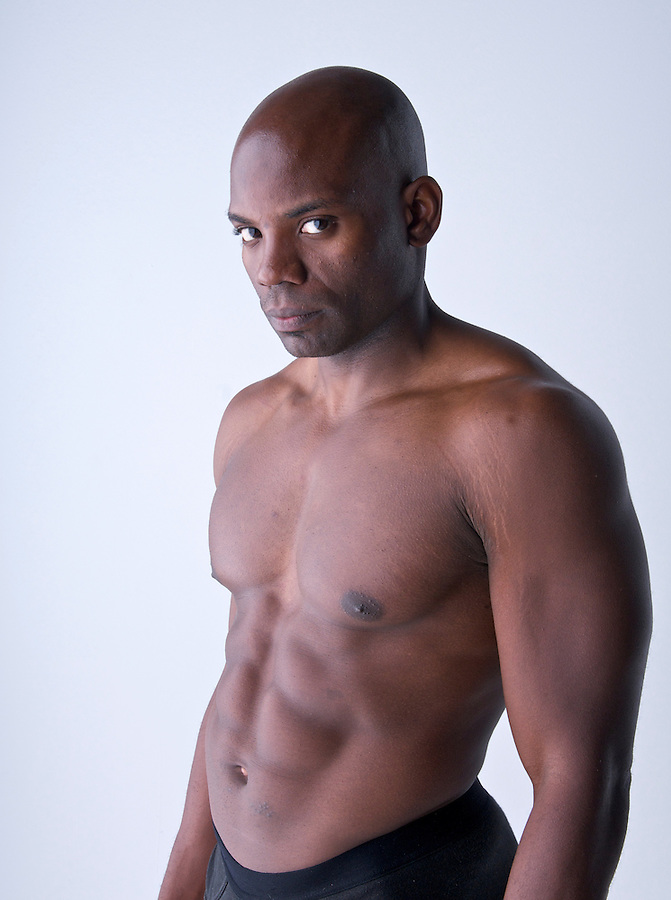 Portrait of young body builder african american looking at camera, white background.