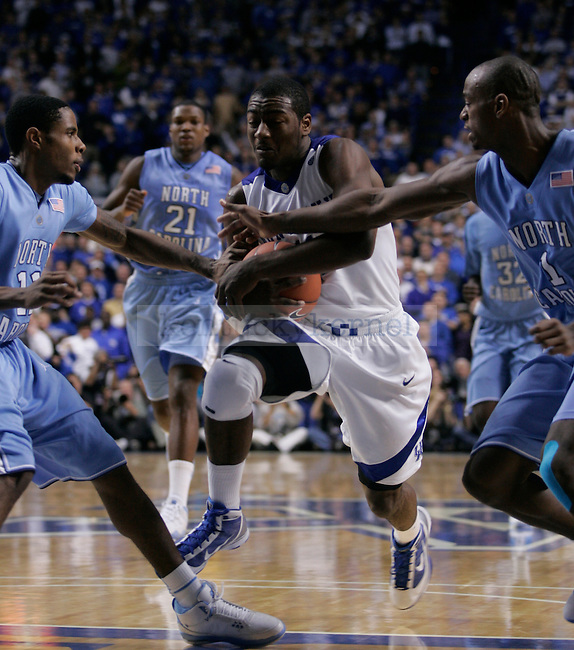 University of Kentucky freshman guard John Wall drives through UNC's Marcus Ginyard, right, and Larry Drew in UK's 68-66 win over the Tar Heels on Saturday, Dec. 5, 2009 in Rupp Arena...Photo by Ed Matthews | Staff
