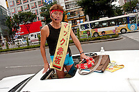 "Mac Akusaka campaigning in Shibuya. real name, Makoto Tonami, he is chairman of the ""Smile Therapy Association Foundation."" and is the sole candidate of the ""Japan Smile Party."" Akasaka's policies call for the dissolution of Japan's Self Defense Forces and a lowering of the voting age. He believes these measures will help bring about an increase in happiness in Japan's population. Shibuya, Tokyo, Japan June 26th 2010 Makoto Tonami, known as Mac Akasaka campaigning for election in Shibuya. He is chairman of the ""Smile Therapy Association Foundation."" and the sole candidate of the ""Japan Smile Party."" Akasaka's policies call for the dissolution of Japan's Self Defense Forces and a lowering of the voting age. He believes these measures will help bring about an increase in happiness in Japan's population. Shibuya, Tokyo, Japan June 26th 2010"