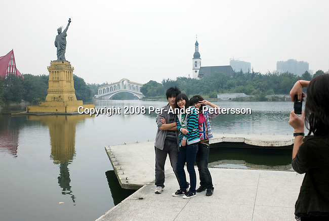 CHENGDU, CHINA OCTOBER 9: Student stands in front of a copy of The Statue Of Liberty at Chengdu World Paradise Theme Park on October 9, 2008 in Chengdu, China. The park closed in 2004 due to lack of funds and visitors. Some of the attractions are still there such as a Statue Of Liberty and Rialto bridge from Venice, Italy. Now its serves as a College and many students and teachers live there. Chinese people love theme parks and new ones are opening constantly. It's estimated that there's about 2400 theme parks in the country. Because of the tougher competition, some parks close down. (Photo by Per-Anders Pettersson) .