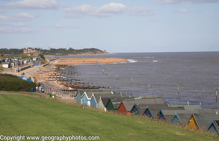 Coastal defences, Felixstowe, Suffolk, England. A view looking north towards the mouth of the River Deben showing beach huts and beaches defended from erosion by wooden groynes.