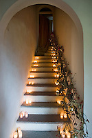The staircase is atmospherically lit with groups of tealights on each step and the handrail is decorated with branches and red winter berries