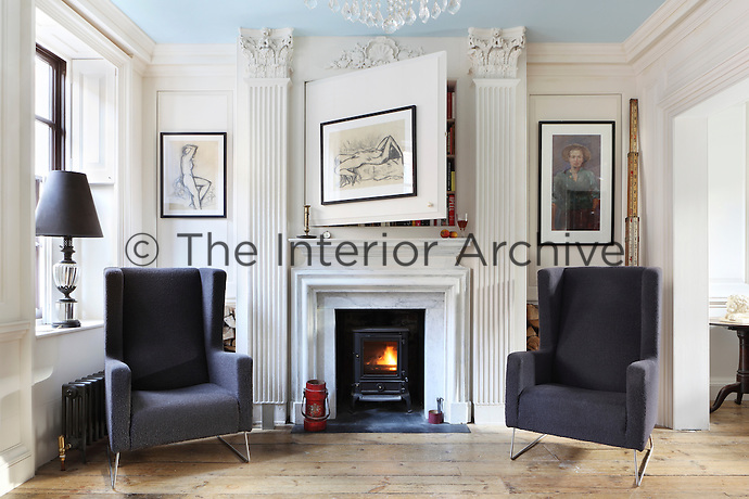 A pair of oversize contemporary armchairs flank a faux marble fireplace in the living room