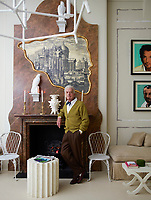 Nicky Haslam in his living room. A faux marble panel surrounds a real marble fireplace and an engraving of a Piranesi-style ruin is outlined in an irregular gilded frame whose shape echoes a Cocteau drawing. Resin falcons are painted white to mimic porcelain and a pair of Warholesque portraits of the owner by the artist Skid Stewart hang over a daybed.
