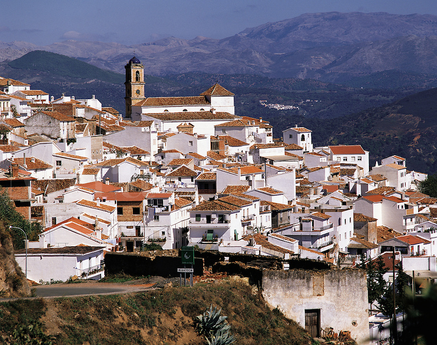 The church-steeple rises above the pretty white village of Algotocin, southern Spain, with a background of distant hills