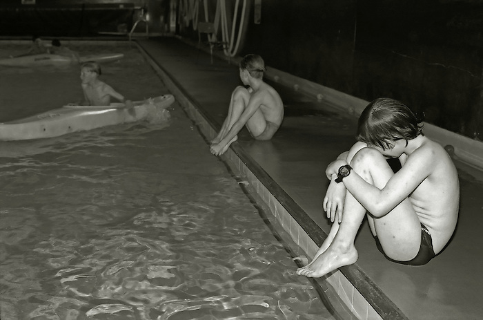Two boys wait their turn for canoe lessons in an indoor swimming pool...Kent,England.1994.