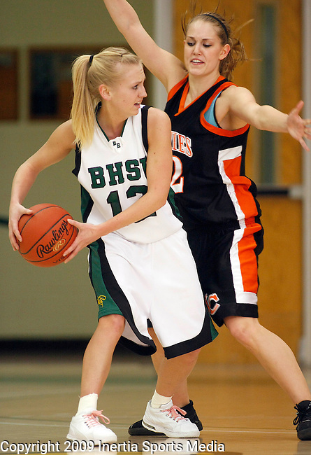 SPEARFISH, SD - FEBRUARY 25, 2009 --  Janna Schriber #12 of Black Hills State looks past Jamestown College defender Amanda Rantapaa #22 during their Dakota Athletic Conference semi-final game Wednesday evening at the Young Center.  (Photo by Dick Carlson/Inertia)