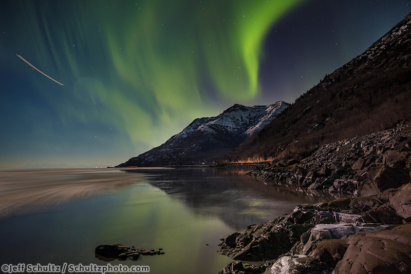 winter landscape shows Northern Lights (Aurora Borealis) in sky above moonlight on the Chugach Mountains and reflected in Turnagain Arm along   Seward Highway January 2014