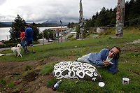 John paints a rock of petroglyph carvings his elders have cared for in the Totem Park. He is helping prepare for the totem raising in town where 1000 people are expected.  .Ron Williams paints a rock of petroglyph carvings his elders cared for in the Tlinget Totem Park. He is helping prepare for a historic totem raising in town where 1000 people celebrated the addition of seven poles..