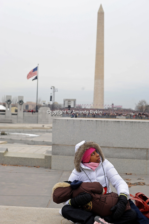 "A woman sits with her child during the ""We Are One"" concert in celebration of Barack Obama's inauguration as president of the United States at the Lincoln Memorial in Washington, DC on January 18, 2009."