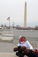 """A woman sits with her child during the """"We Are One"""" concert in celebration of Barack Obama's inauguration as president of the United States at the Lincoln Memorial in Washington, DC on January 18, 2009."""