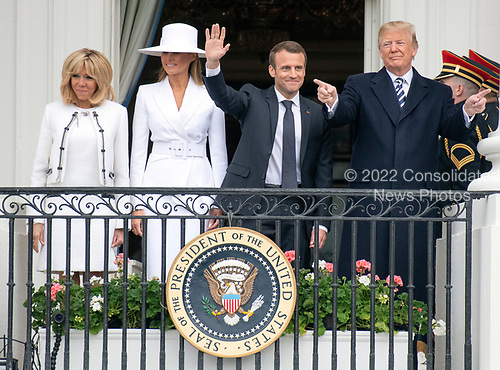 United States President Donald J. Trump, right, and first lady Melania Trump, left center, and President Emmanuel Macron of France, right center, and his wife, Brigitte Macron, left, wave to the crowd as they pose for a group photo following an arrival ceremony on the South Lawn of the White House in Washington, DC on Tuesday, April 24, 2018.<br /> Credit: Ron Sachs / CNP
